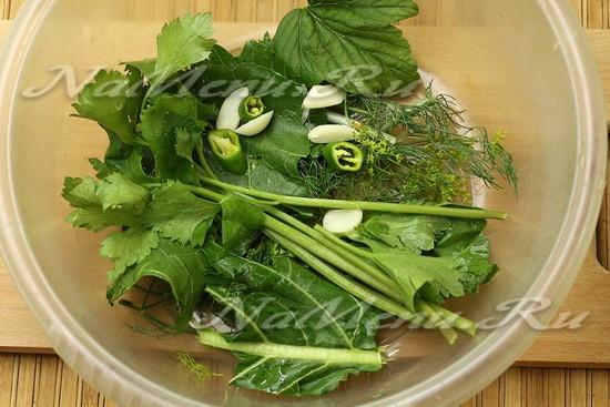 Вниз укладываем слой пряной зелени, насыпаем немного чеснока и перчика.