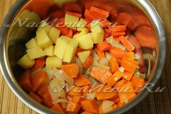 Высыпаем в кастрюлю картофель и кусочки моркови