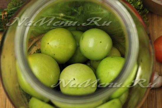 Укладываем на дно банки зеленые помидоры в 2-3 слоя