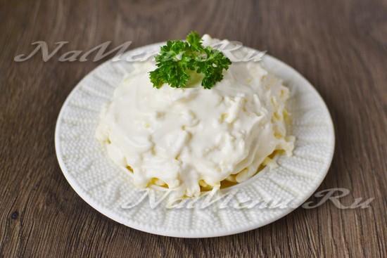 Выкладываем тертый сырок в салатник и сверху смазываем чесночным майонезом.