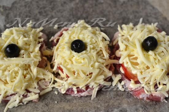 Посыпаем теперь мясо тёртым сыром, а в центр ананаса кладём маслину