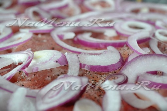 Выложить лук на мясо
