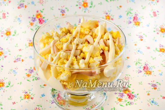 Выложить слой картошки, кальмаров и яиц
